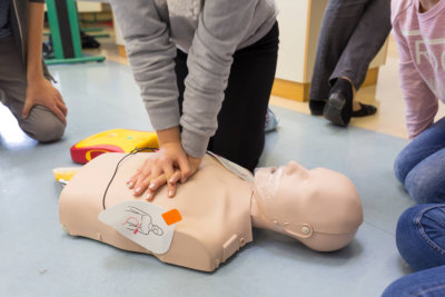 a person practicing cpr on a dummy